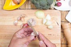 Chef is peeling garlic Royalty Free Stock Photography