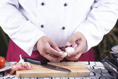 Chef peeling garlic with hand Royalty Free Stock Photos