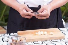 Chef is peeling garlic / Stock Images
