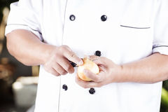 Chef peeling the onion Royalty Free Stock Photography