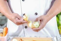 Chef peeling onions Royalty Free Stock Photos