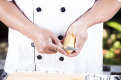 Chef peeling Potato with knife Royalty Free Stock Images