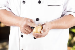Chef peeling Potato with knife Stock Photo