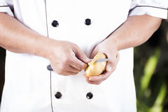 Chef peeling Potato with knife Stock Photography