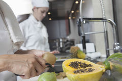 Chef Peeling Tropical Fruit In Kitchen. Closeup of female chef peeling tropical fruit with colleague working in background Royalty Free Stock Photography