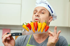 Chef with peppers on knife. Male chef holding colorful small pepperes on his knife Royalty Free Stock Photo