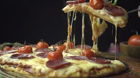 Chef picks up a slice of pizza with cheese slow motion