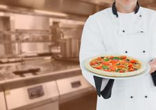 Chef with pizza against blurry kitchen with orange overlay Royalty Free Stock Photography