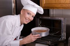 Chef places cake in oven. Assertive posed smiling female Pastry Chef placing a floury cake pan of devil's food batter into an oven Stock Images