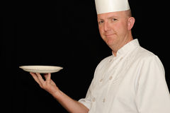 Chef with plate. A chef in white uniform showing an empty plate, black background Stock Images