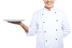 Chef with plate. Close-up of confident mature chef in white uniform holding empty plate and smiling while standing against white background Stock Images