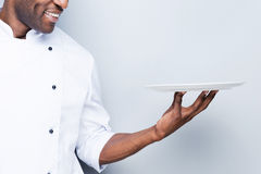 Chef with plate. Close-up of confident young African chef in white uniform holding empty plate and smiling while standing against grey background Stock Image