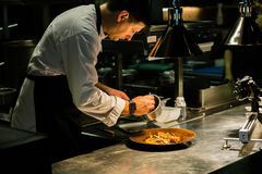 Chef plating dish on kitchen counter while recording at kitchen hotel.  stock images