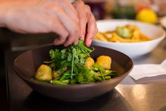 Chef plating fresh ricotta gnocchi in an Italian restaurant. Chef plating fresh ricotta gnocchi in an Italian restaurant stock photo