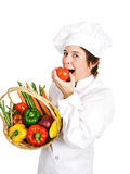 Chef - Plump Ripe Tomato. Chef holding a basket of fresh vegetables takes a bit out of a ripe tomato.  Isolated on white Stock Photos