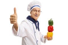 Chef plus âgé avec des poivrons faisant un pouce vers le haut de geste Photo libre de droits