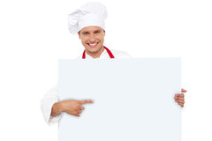 Chef pointing at the blank white billboard Royalty Free Stock Image