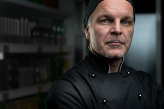 Chef portrait. Attractive chef portrait in black uniform on dark background Stock Image