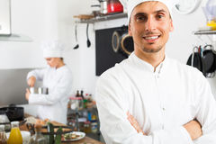Chef posing at cafe`s kitchen. Portrait of glad young men dressed as chef standing at cafe`s kitchen royalty free stock photos