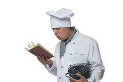 Chef with pot in his hand a recipe book looks Royalty Free Stock Photos