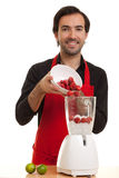Chef pour blender. A chef pouring some strawberries into a blender royalty free stock photos
