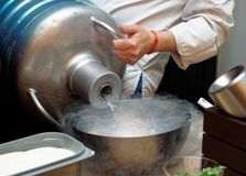 Chef is pouring liquid nitroden from a large Dewar vessel Stock Photography