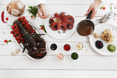 Chef pouring octopus with special sauce, flat lay Royalty Free Stock Photos
