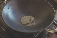 Chef pouring oil in to the frying pan for cooking Royalty Free Stock Image