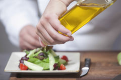 Chef Pouring Olive Oil Over Salad Stock Image