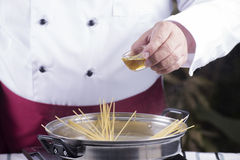 Chef pouring olive oil to spaghetti boiled in the pan Stock Photo