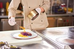 Chef pouring orange sauce on meat. Royalty Free Stock Image