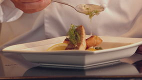 Chef pouring sauce over fish dish stock video