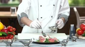 Chef pouring sauce on salad. Food preparation, cooking table stock video footage