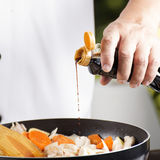 Chef pouring shoyu sauce to the pan for cooking Japanese pork cu Royalty Free Stock Image
