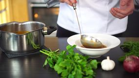 Chef pouring soup in a plate and decorating with herbs stock video footage