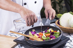 Chef pouring soup to the pan Stock Photo