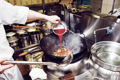 Chef is pouring sour sauce in wok Royalty Free Stock Photo