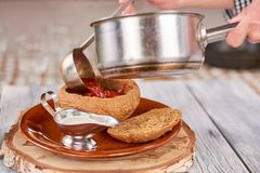 Chef pouring ukrainian borshch in bread pot. Chef putting from saucepan red soup in pot from bread. Traditional ukrainian food Stock Images