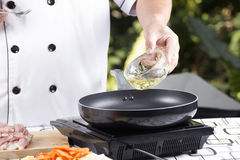 Chef pouring vegetable oil to the pan Stock Photos