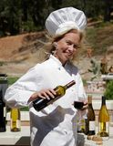 Chef pouring wine. Female Chef pouring wine outdoors Stock Photo