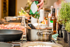Chef pours brown sugar into the pot while cooking. In a professional kitchen Stock Photo