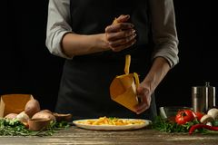 The chef pours into the envelope the french fries ready, freeze, on the background with vegetables. Cooking tasty but harmful food royalty free stock image