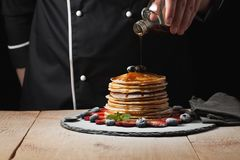The chef pours maple syrup on pancake stack with blueberries and strawberries on black background royalty free stock photos