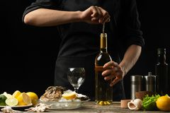 Chef pours, tastes Italian dry oyster wine with lemon royalty free stock photo