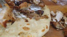 Chef préparant le burrito ou le shawarma avec le poulet et les légumes grillés sur le fond en bois banque de vidéos