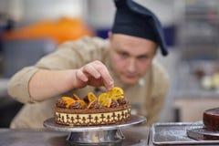 Chef préparant le gâteau de désert dans la cuisine Photographie stock libre de droits