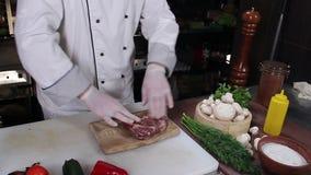Chef préparant le morceau de viande pour faire cuire sur le gril de barbecue banque de vidéos