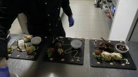 Chef préparant trois plats dans la cuisine du restaurant garnissant et décorant les plats banque de vidéos