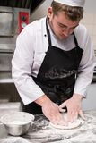 Chef prepare traditional pizza dough flour messy. Chef preparing traditional italian pizza dough, his hands and apron covered in flour. Cooking can be messy Stock Image