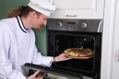 Chef prepared italian pizza in kitchen Stock Photos
